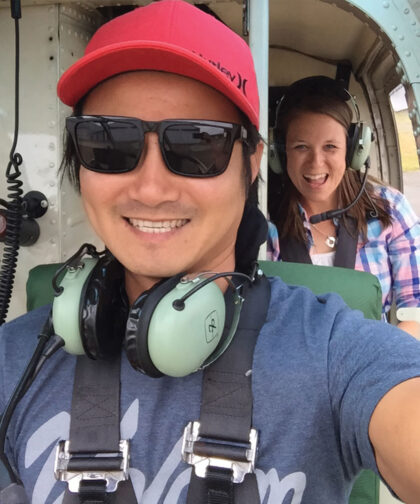 A man and woman sitting one in front of the other smile during a helicopter ride.