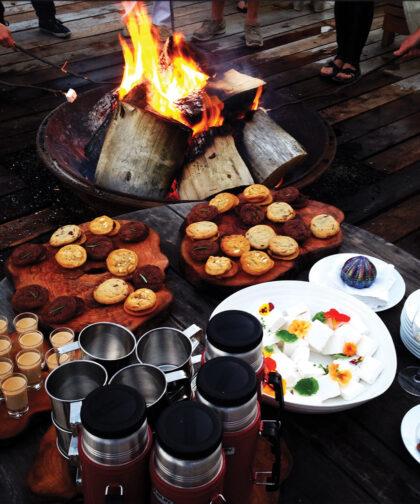 Beside a roaring campfire is a table holding food and drinks.