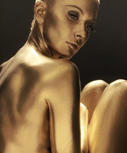 A woman painted gold looks over her shoulder.