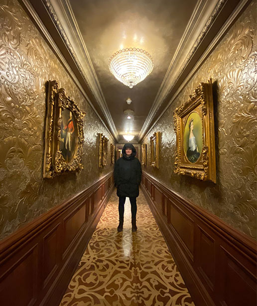 A man stands in a beautifully ornate hallway in one of the Vintage Hotels properties.