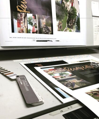 Print materials, colour swatches, and a computer screen show a campaign in progress.