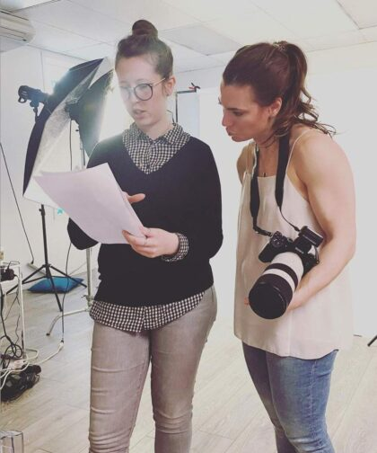Two women reviewing a shot list in a photo studio