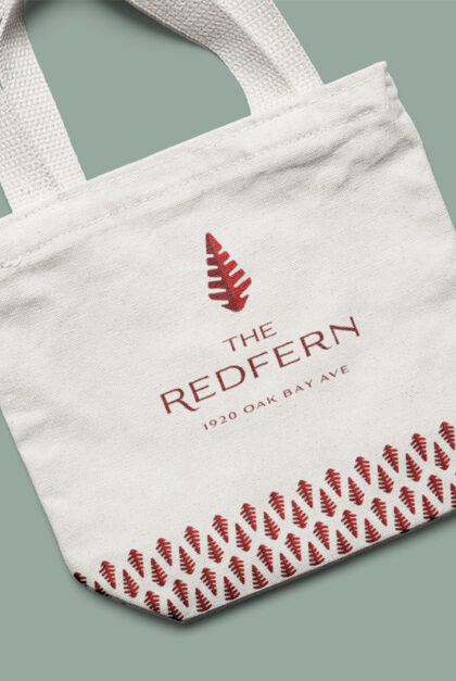 A tote bag featuring The Redfern name, logo, and building address.
