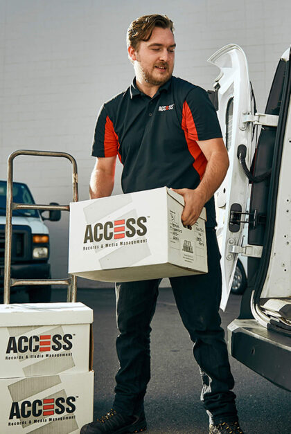 A man holds a box that says Access. Two other boxes are stacked nearby..