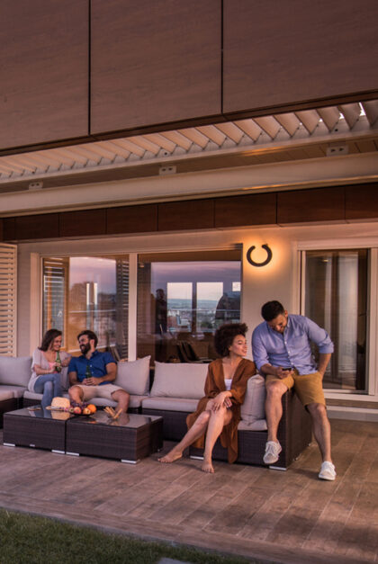 Four people relax on a couch on an outdoor patio.