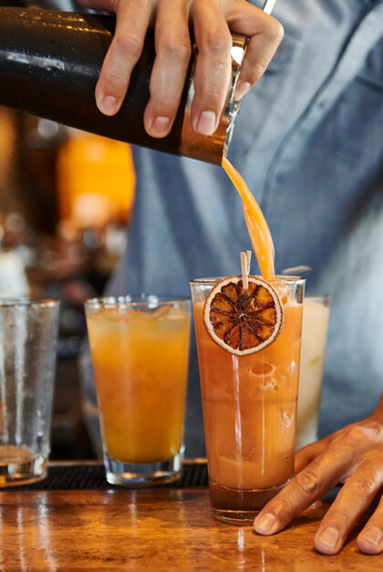 A close up of someone pouring an orange cocktail into a glass.