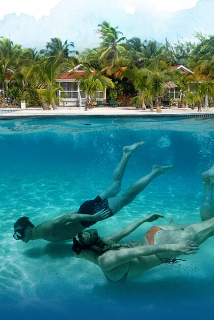 Two people swim under clear waters.