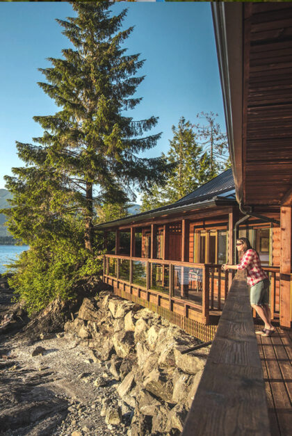 A woman looks out from the deck of a cabin.